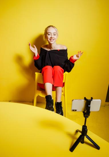 Young fashion girl blogger dressed in red trousers and black jacket takes a selfie on the smartphone standing possing sitting on the stool in the room with yellow walls and furniture .